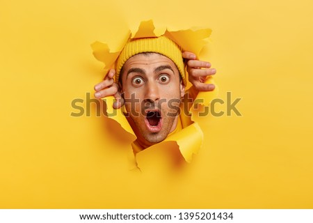 Headshot of stupefied young man with European appearance, wears yellow hat, keeps head in torn paper wall, keeps jaw dropped from surprisement, impressed by sudden bad news or rumor. Omg concept #1395201434