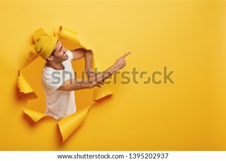 Isolated shot of satisfied male model stands sideways in paper hole, dressed in yellow headgear, white t shirt, points on blank space with index finger, advertises item. Look at this awesome product