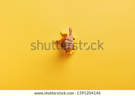 Image of unrecognizable man makes thumb up gesture, demonstrates approval or agreement, gestures through torn paper wall yellow background. Body language concept. Hand sign. Hole in wall. Like gesture #1395204146