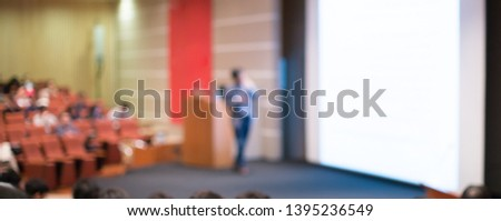 Blurred business presentation with keynote speaker near blank white screen. Seminar concept background with executive leading workshop in conference hall. Presenter in lecture to audience.