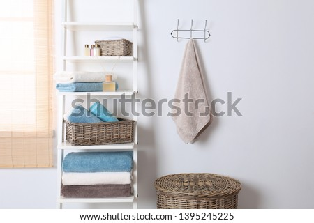 Shelving unit and rack with clean towels and toiletries near white wall Royalty-Free Stock Photo #1395245225