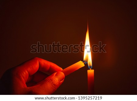 The hand that is lighting candles in the dark With burning candles shining the light at night  Design for the background, Burning candle on black background, Candle in hand, Candle in the dark. #1395257219
