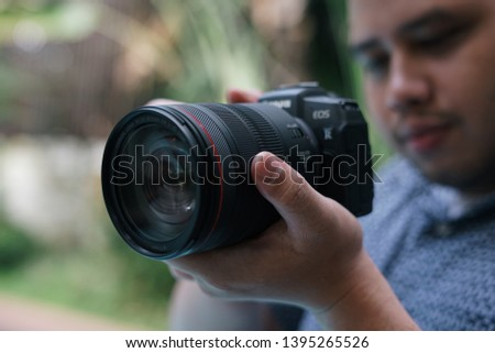 Jakarta, Indonesia - May 12, 2019: Photographer taking pictures with Canon EOS RP full frame mirrorless camera. #1395265526