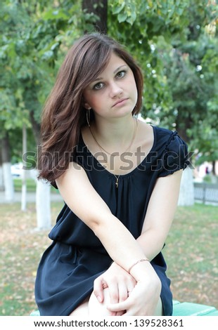 Attractive young girl sitting on a park bench #139528361