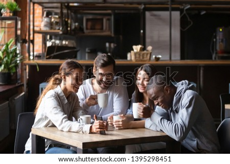 Diverse friends having fun in cafe together, looking at smartphone screen, watching funny video or photo, drinking coffee, attractive smiling women and men laughing at joke in social network #1395298451