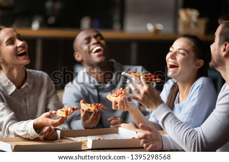 Diverse friends eating pizza, happy colleagues or students having fun together in cafe, men and women laughing at funny joke, holding Italian junk food slices in hands at meeting in cafeteria #1395298568