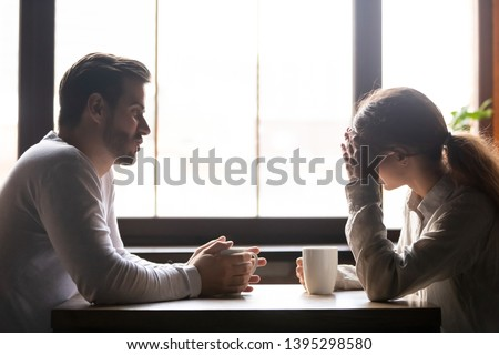 Upset woman and man talking in cafe about problem in relationships, frustrated girlfriend hiding face in hands, couple sitting at table in coffeehouse together, drinking coffee, bad first date #1395298580