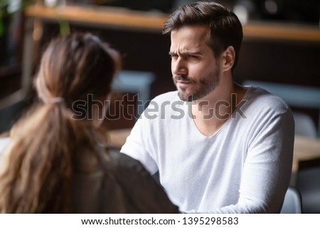 Doubting dissatisfied man looking at woman, bad first date concept, young couple sitting at table in cafe, talking, bad first impression, new acquaintance in public place, unpleasant conversation #1395298583