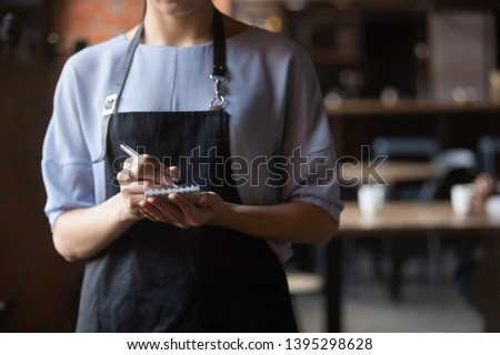 Close up attractive waitress wearing black apron standing in cozy coffeehouse, female cafe worker with notebook in hands waiting for, ready to take customers, guests order in restaurant #1395298628