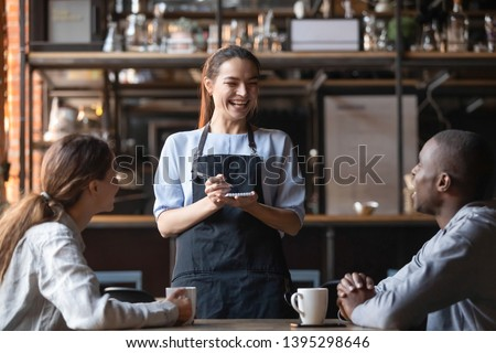 Attractive waitress laughing at African American man funny joke, serving customers, diverse couple making order in cafe, coffeehouse female worker and multiracial visitors having fun #1395298646
