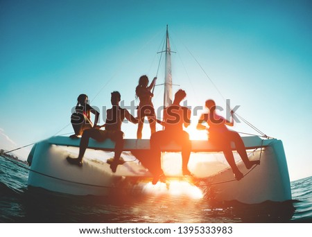 Silhouette of young friends chilling in catamaran boat - Group of people making tour ocean trip - Travel, summer, friendship, tropical concept - Focus on two left guys - Water on camera #1395333983