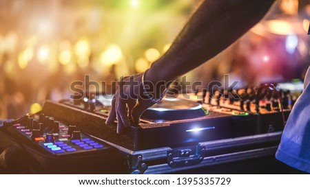 Dj mixing outdoor at beach party festival with crowd of people in background - Summer nightlife view of disco club outside - Soft focus on hand - Fun ,youth,entertainment and fest concept Royalty-Free Stock Photo #1395335729