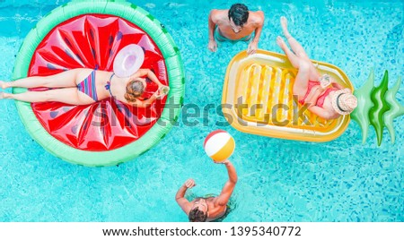 Happy friends playing with air lilo ball inside swimming pool - Young people having fun on summer holidays vacation - Travel, generation trends youth lifestyle, friendship and tropical concept #1395340772