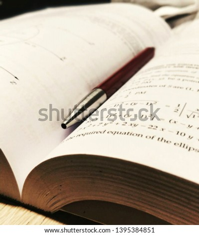 It is a image of mathematics book with a parker pen at its mid . #1395384851