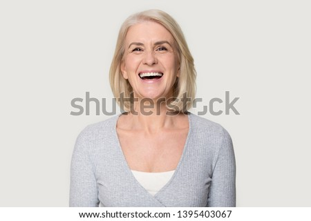 Head shot portrait overjoyed blond middle aged female smiling look at camera laughing feels happy pose isolated on grey studio background, advertise clinic procedure dental care prosthesis for seniors #1395403067