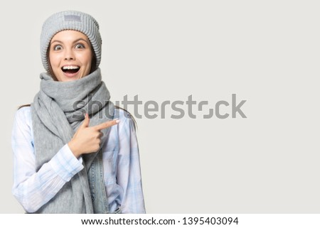 Girl in hat scarf point finger at copy space white studio background, girl advertise fashion store, super offer, discount cheap prices, seasonal clearance bargain sale, sell-out, Black Friday concept