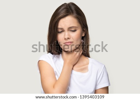 Tonsillitis angina concept image head shot studio portrait on grey background unhealthy woman touch neck feels discomfort painful feelings hard to swallow, sore throat pain irritation or loss of voice Royalty-Free Stock Photo #1395403109