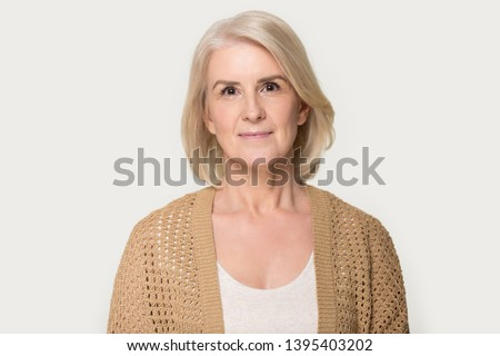Head shot portrait attractive mature fifty year woman wearing brown knitted cardigan pose on grey studio background, healthy retired female natural beauty, health care, medical insurance concept image #1395403202