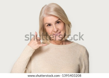 Head shot studio portrait isolated on grey background middle aged attractive woman look at camera imitate phone makes with hand call me gesture mobile device connection and communication concept image #1395403208