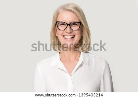 Head shot portrait laughing old businesswoman in glasses white blouse looks at camera feels happy pose isolated on grey studio background, experienced professional business coach teacher concept image