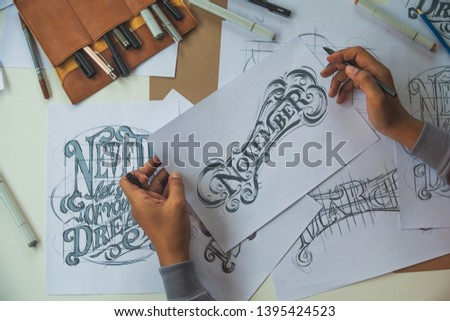 Typography Calligraphy artist designer drawing sketch writes letting spelled pen brush ink paper table artwork.Workplace design studio. #1395424523