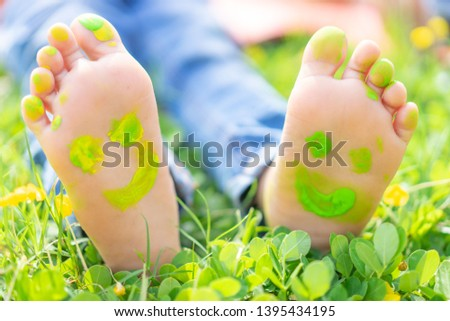 Image of human foots in colorful paint with smiles.Child lying on green grass.asian  kid having fun outdoors in spring park