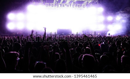 Back view of crowd of people having fun in front of illuminated stage at music concert by night. Copy space. #1395461465