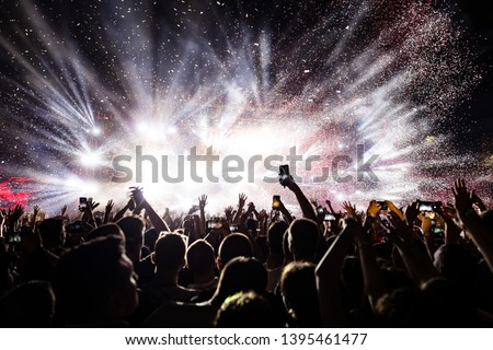 Excited audience watching confetti fireworks and having fun on music festival at night. Copy space.  Royalty-Free Stock Photo #1395461477