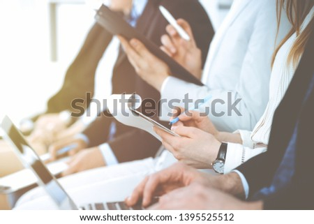 Business people working at meeting or conference, close-up of hands. Group of unknown businessmen and women in modern white office. Teamwork or coaching concept #1395525512