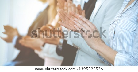 Business people clapping and applause at meeting or conference, close-up of hands. Group of unknown businessmen and women in modern white office. Success teamwork or corporate coaching concept #1395525536