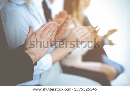 Business people clapping and applause at meeting or conference, close-up of hands. Group of unknown businessmen and women in modern white office. Success teamwork or corporate coaching concept #1395525545