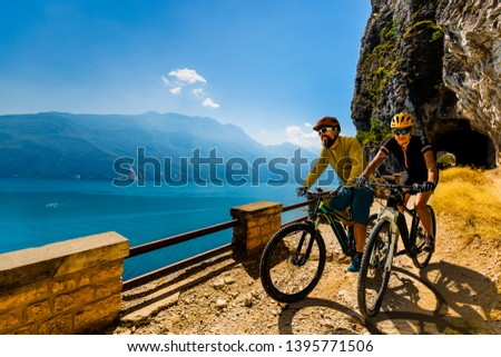 Cycling woman and man riding on bikes at sunrise mountains and Garda lake landscape. Couple cycling MTB enduro flow sentiero ponale trail track. Outdoor sport activity. #1395771506