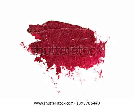 Red wine colored glitter lipstick smear isolated on white background. Shimmering makeup texture. Beauty and makeup concept.