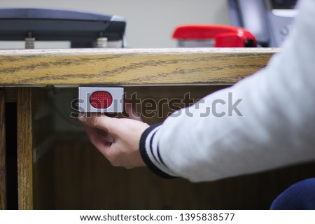 A hand ready to press a panic button under an administrative desk Royalty-Free Stock Photo #1395838577