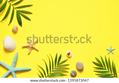 Summer vibes. Tropical palm leaf, seashells and starfish. Flat lay, top view. Yellow summer background.Summer concept.