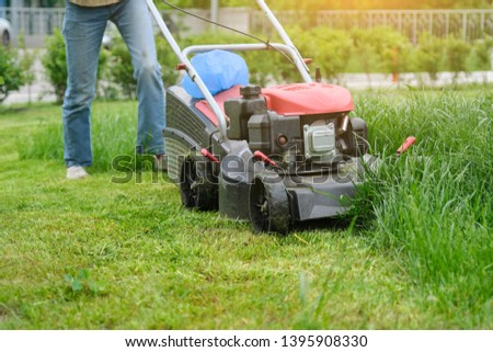 Gardener woman legs mowing grass with lawnmower, city courtyard of an apartment building. #1395908330