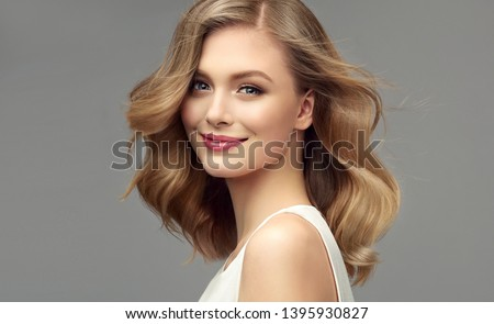 Blonde woman with curly beautiful hair  on gray background. The girl with a pleasant smile. Short haircut . Bob hairstyle  #1395930827