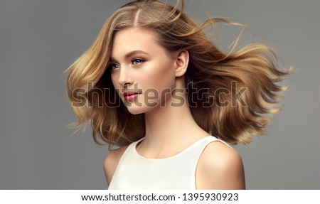 Blonde woman with curly beautiful hair  on gray background. The girl with a pleasant smile. Short haircut . Bob hairstyle  #1395930923