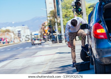 A strong businessman is bending his knee while trying to change a flattie on his car with his lug wrench. #1395932576