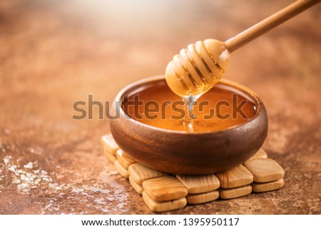 Honey dripping from honey dipper in wooden bowl.  Close-up. Healthy organic Thick honey dipping from the wooden honey spoon, closeup #1395950117