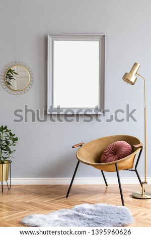 Stylish and luxury interior with design honey yellow armchair, gray mock up frame, gold lamp, mirror, plant, pillow and elegant accessories. Modern home decor of living room. Real photo. Template.
