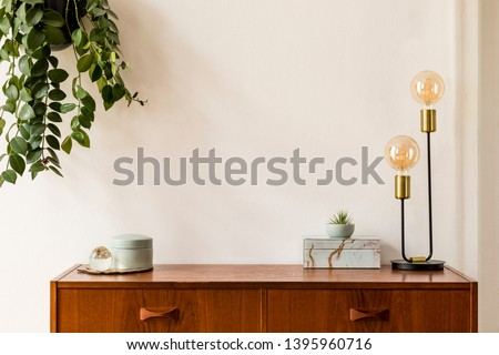 Stylish and design space of home interior with vintage cupboard, marble elegant accessories, hanging plant and gold table lamp. Cozy home decor. Minimalistic concept. Copy space. Real photo, Template. #1395960716