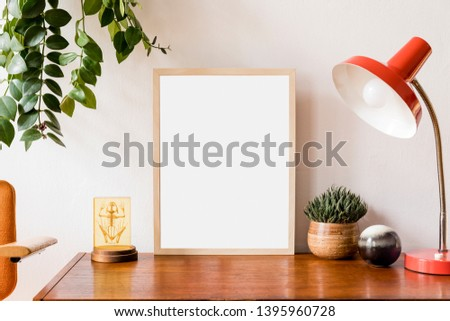Stylish room of home interior with brown mock up frame with vintage accessories, plant,cacti, chair and red retro table lamp. Cozy home decor. Minimalistic concept. Modern composition of cupboard. #1395960728