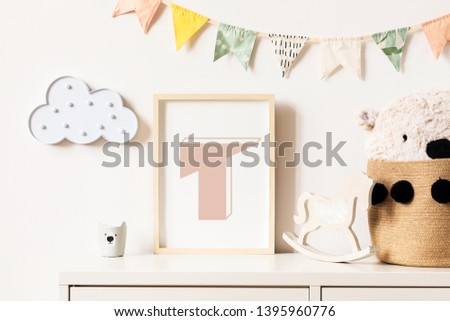 The modern scandinavian newborn baby room with mock up photo frame, wooden toy, plush teddy bear and wooden horse. Hanging cotton flags and cloud. Minimalistic and cozy decor of childroom.