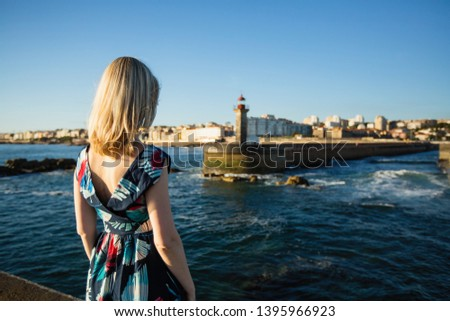 Beautiful blonde woman in a long dress standing on the seafront. #1395966923