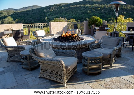 Chairs and side tables around fire pit for gathering. #1396019135
