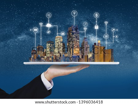 Smart city, building technology, and real estate business. Businessman holding digital tablet with buildings hologram and application programming interface technology #1396036418