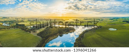 Sun setting over scenic Australian countryside grasslands and pastures with river passing through - aerial panorama Royalty-Free Stock Photo #1396041266