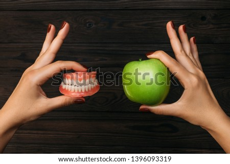 Denture and Apple in the hands of a doctor. False teeth denture against green granny smith apple. Dental prosthesis care. Dental care. Beautiful tooth. Prosthetics. False teeth #1396093319