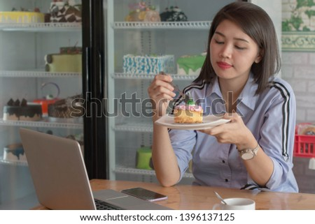 attractive asian female enjoying slice of strawberry cake at cake store with laptop, smartphone and cup of coffee in the morning inside cafe #1396137125